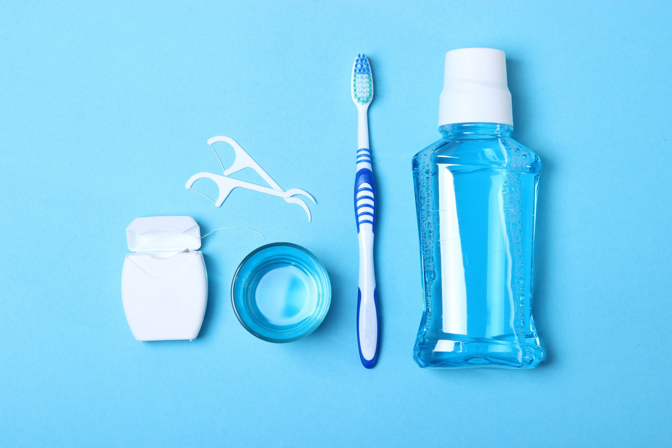 oral care instruments and fluoride on blue background